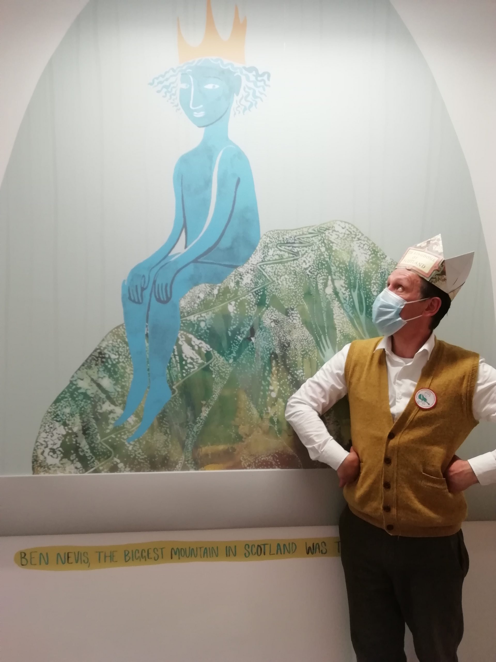 Andy Cannon wearing a crown and looking at a wall painting
